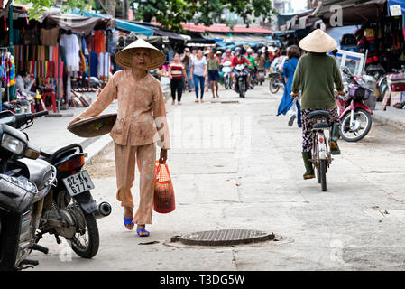 Vietnamese woman in traditional clothes walking around the street market in Hoi An, Vietnam - Stock Photo