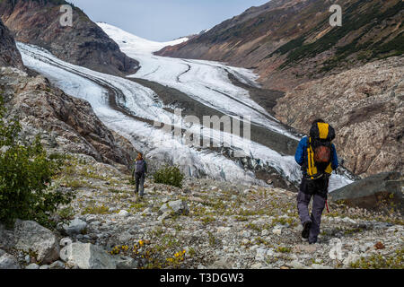 Trekking above a large glacier in the Boundary Mountain Range of Canada. A young man and woman hike along a ridge overlooking a glacier in British Col - Stock Photo