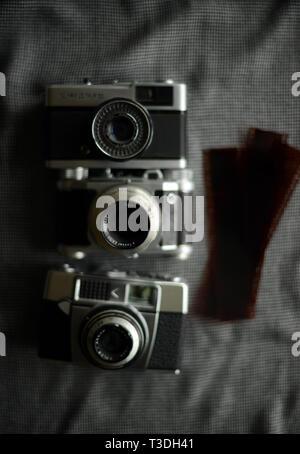 three antique vintage film cameras and film negatives