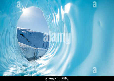 Deep in the Alaskan wilderness, far back on the Matanuska Glacier, the sun shines into the entrance of a large ice cave. The rounded, blue cavern shin