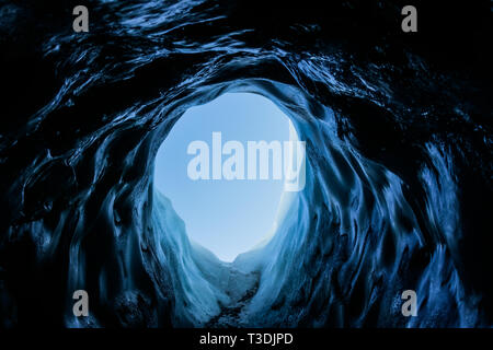 Looking out of a small, dark tunnel of an ice cave entrance on the Matanuska Glacier in Alaska. The cave is very dark, but light from the clear sky sh - Stock Photo