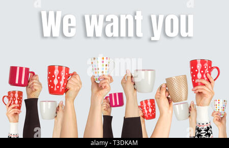 many hands raised up and holding ceramic cups on a gray background,  inscription we want you, the concept of recruitment in the company - Stock Photo
