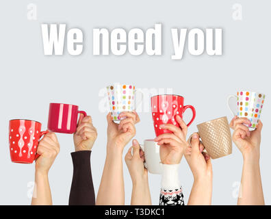 many hands raised up and holding ceramic cups on a gray background,  inscription we need you,  concept of recruitment in the company - Stock Photo