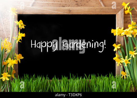 Blackboard With English Text Happy Gardening. Sunny Spring Flowers Nacissus Or Daffodil With Grass. Rustic Aged Wooden Background. - Stock Photo