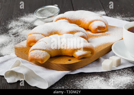 Biscuit rolls filled with jam with powdered sugar on top on plate over wooden table - Stock Photo