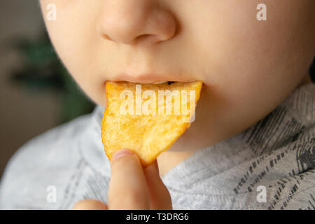 Baby eating chips. Close-up. The child holds the chips. Junk food. - Stock Photo