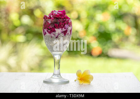 Chia seeds pudding with red dragon fruit and white yogurt in a glass for breakfast on the background of nature, close up. The concept of healthy eatin - Stock Photo
