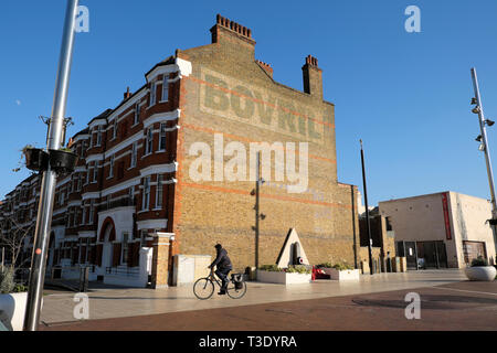 Man on bike cyclist cycling in Windrush Square and the Bovril building next to Black Cultural Centre in Brixton South London England UK  KATHY DEWITT - Stock Photo