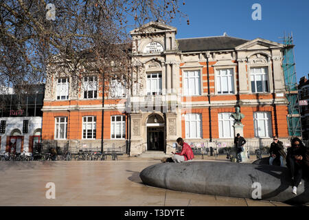 Person sitting reading outside the Tate Central Free Library building in Brixton South London SW2 England UK  KATHY DEWITT - Stock Photo