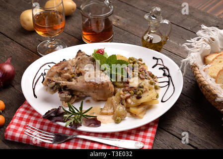 chicken legs with potatoes and spices on wood - Stock Photo