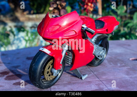 a isolated closeup red toy motorcycle with cold colors. photo has taken from a garden. - Stock Photo