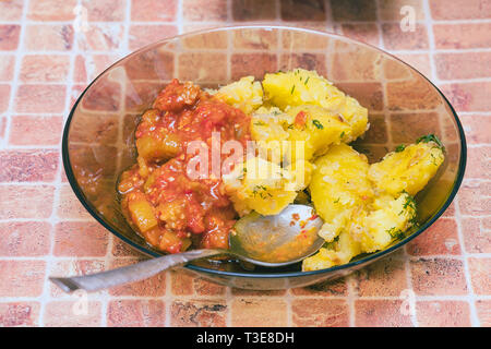 Potatoes with vegetables in a plate with a spoon on the table - Stock Photo