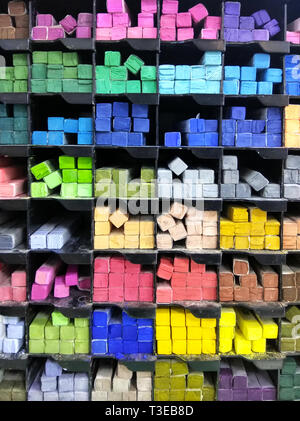 Colourful pieces of pastel chalks on the shelf - Stock Photo