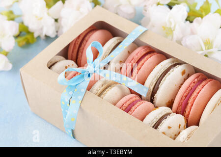Pink macarons in a box decorated with ribbon and flowers on blue background. French dessert. - Stock Photo
