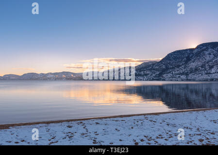 Sunset colors and snow covered mountains reflected in calm lake with snow covered beach - Stock Photo