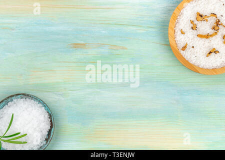 Various types of salt with different addings, shot from the top on a teal blue background, forming a frame with a place for text - Stock Photo