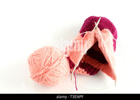 pink and red tangle of thread for hand knitting and a pair of knitting needles on a white background close-up - Stock Photo