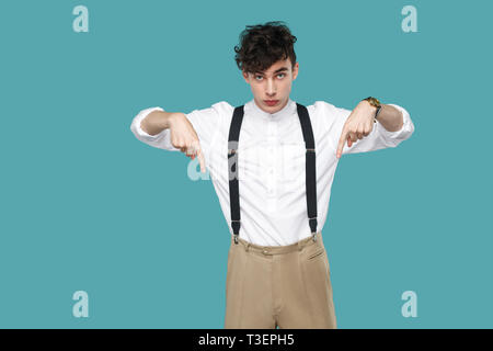 Here and right know. serious man pointing down and looking at camera. Portrait of handsome hipster curly young businessman in classic white shirt, sus - Stock Photo