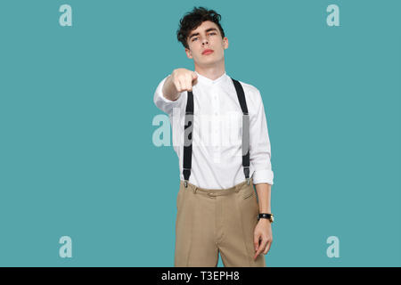 Serious man pointing and looking at camera. Portrait of handsome hipster curly young businessman in classic casual white shirt and suspender standing. - Stock Photo