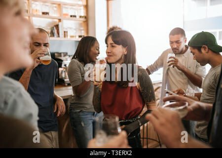 Smiling young woman hanging out with friends in a bar - Stock Photo