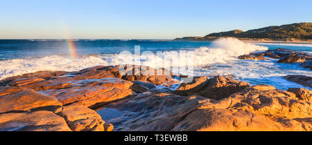 Prevelly Beach, Margaret River. A wave breaking on the shores of Prevelly Beach with a rainbow formed by the sea spray - Stock Photo