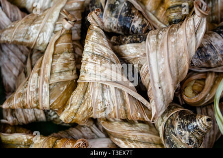Deep fried chicken wrapped in green pandan leaves at street food market in Thailand, close up. Thai food concept - Stock Photo
