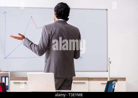 Young handsome businessman in front of whiteboard - Stock Photo