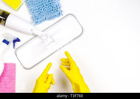 Housework, housekeeping, household, cleaning service concept. Woman hands, cleaning spray mop, rags and sponges on white background - Stock Photo