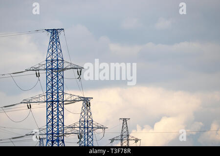 High voltage power line poles with electrical wires on background of evening sky with clouds. Electricity transmission lines, power supply concept