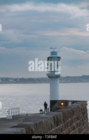 Penzance, Cornwall, UK. 9th Apr, 2019. UK Weather. It was mild and warm for the sunrise at Penzance this morning for this fisherman on the harbour walls at Penzance. Credit: Simon Maycock/Alamy Live News - Stock Photo