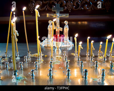 Burning candles before the crucifix in the interior of an Orthodox church