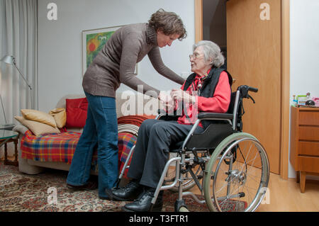 Young woman cares for senior woman sitting in wheelchair - Stock Photo