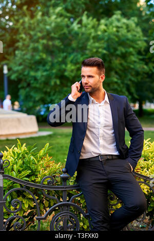 A handsome young businessman leaning against the fence in a park while talking on a phone