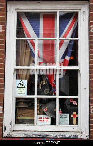 Pawn shop window with air shelter sign, hat, UK Union jack flag, among other second hand objects, Littlehampton, West Sussex, England, UK - Stock Photo