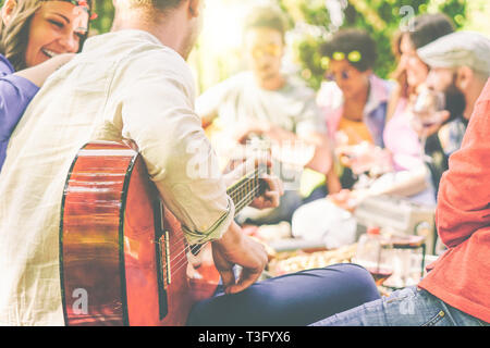 Group of friends having a picnic in a park outdoor - Happy young mates enjoying pic-nic playing guitar, singing and drinking wine eating food - Stock Photo