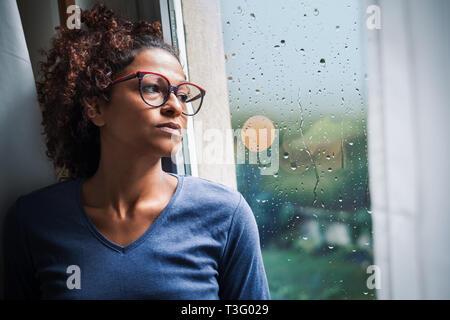 Portrait of pensive black woman standing beside window