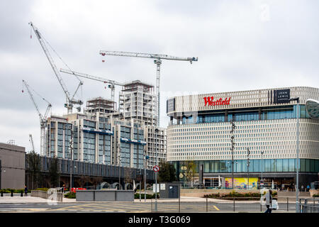 Construction work involving tall cranes behind  the Westfield shopping center at white City, Shepherds Bush, London. - Stock Photo