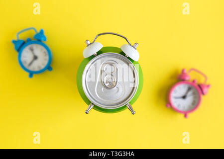 Flat lay of aluminum can in form of alarm clock and colorful alarm-clocks in the background on yellow minimal creative concept. - Stock Photo
