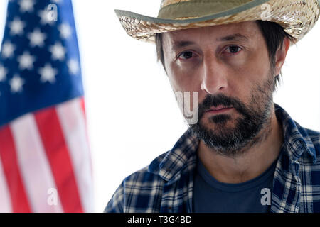 Serious american farmer looking at camera, portrait of adult male person with straw hat and plaid shirt with USA flag in background - Stock Photo
