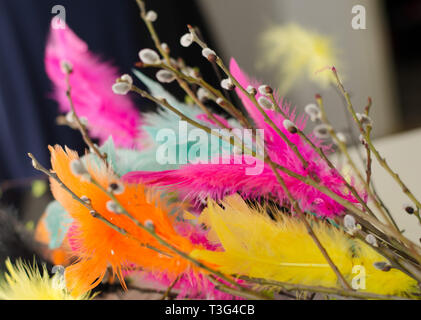 Traditional easter decoration made with twigs with colorful feathers on them - Stock Photo