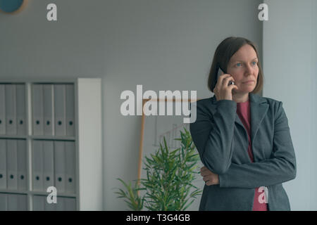Serious businesswoman talking on mobile phone in office and looking out through the window - Stock Photo
