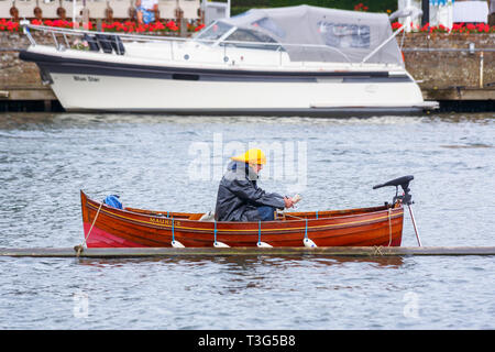 A steward wearing a raincoat and yellow sou'wester hat sits in a wooden rowing boat moored in the River Thames on a wet day at Henley Royal Regatta - Stock Photo