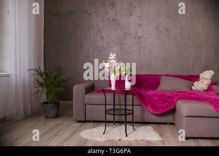Scandinavian Living room design interior with sofa and round table with flowers bouquet.Braun sofa with plaid, pillows, teddy bear.Modern interior - Stock Photo