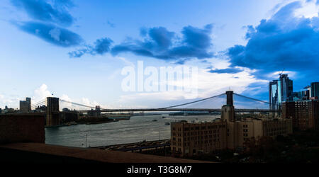Panoramic view of the Brooklyn Bridge spanning the East River beneath a vast blue early-evening sky in Downtown Manhattan, New York City, NY - Stock Photo