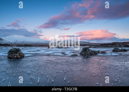 Sunrise over a frozen Lochan na h-achlaise on Rannoch Moor near the enterance to Glencoe in the Scottish Highlands - Stock Photo