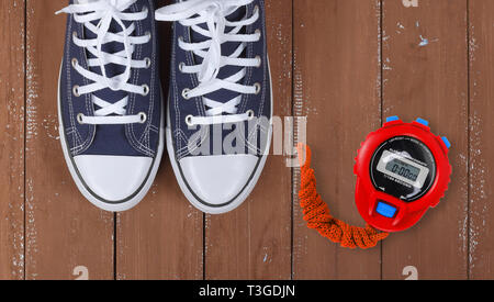Clothes, shoes and sport - top view fragment closeup pair blue gumshoes and Red Stopwatch on a wooden background - Stock Photo