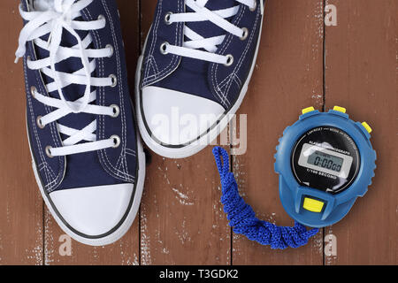 Clothes, shoes and sport - top view fragment closeup pair blue gumshoes and Stopwatch on a wooden background - Stock Photo