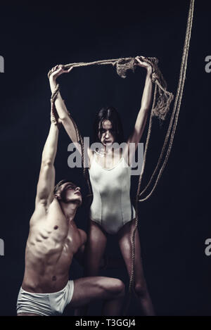 couple of man with muscular body and girl with rope. Circus gymnasts at pilates or yoga training. Fitness dieting and flexibility in acrobatics. Sport - Stock Photo