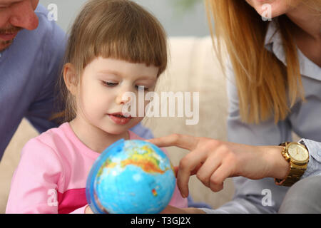Little girl learning about navigation and routs holding globe in arms - Stock Photo
