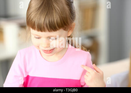 Smiling little girl doing something interesting while playing - Stock Photo